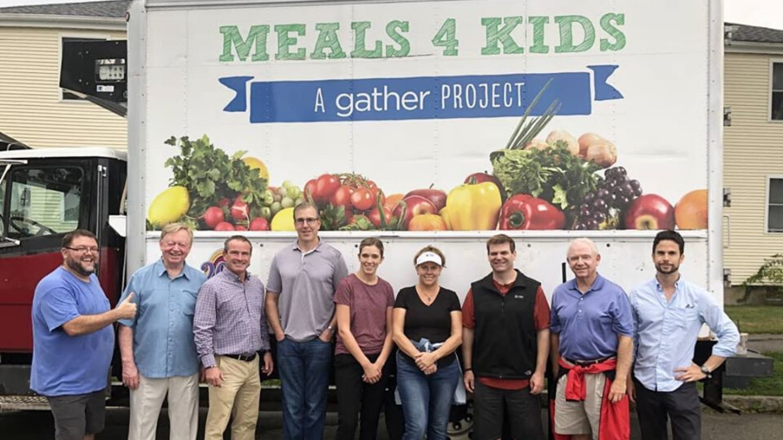 Gather in front of Meals 4 Kids Truck